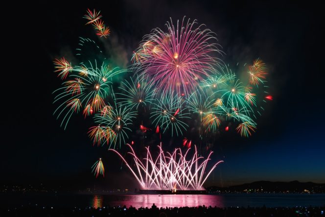 fireworks or red, green and yellow explode above vancouver's Enlgish bay and reflect upon the sea below.