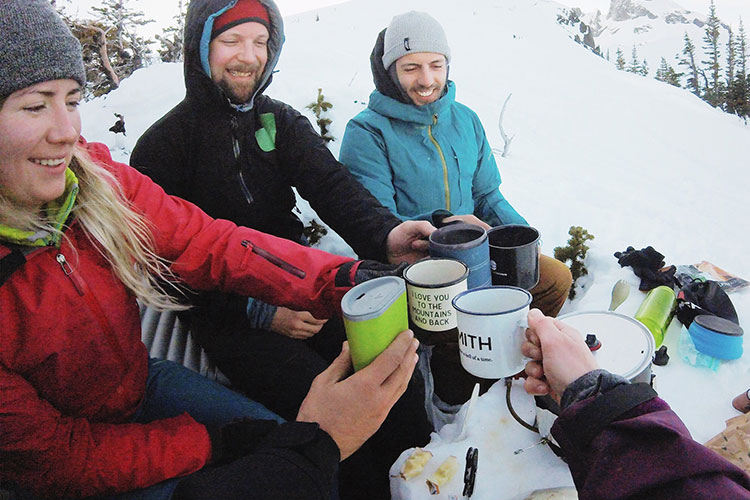 Backcountry skiers cheers with their morning coffees after a night on Black Tusk.