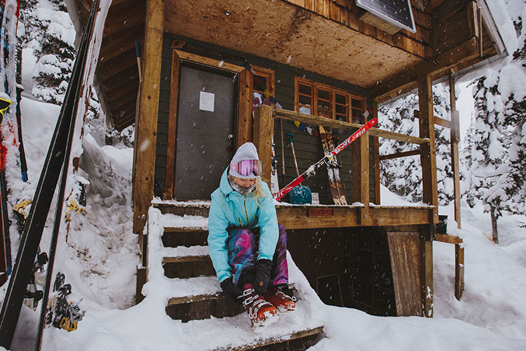 A female skier does up her boots on the steps of a backcountry hut.