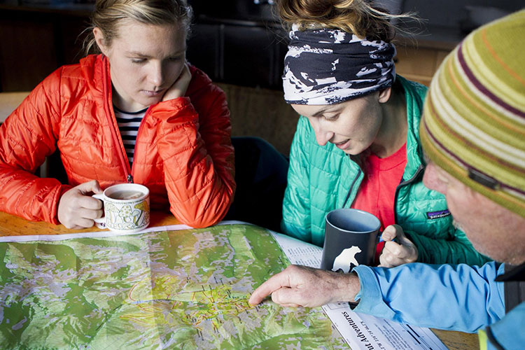 Three people look over a map.