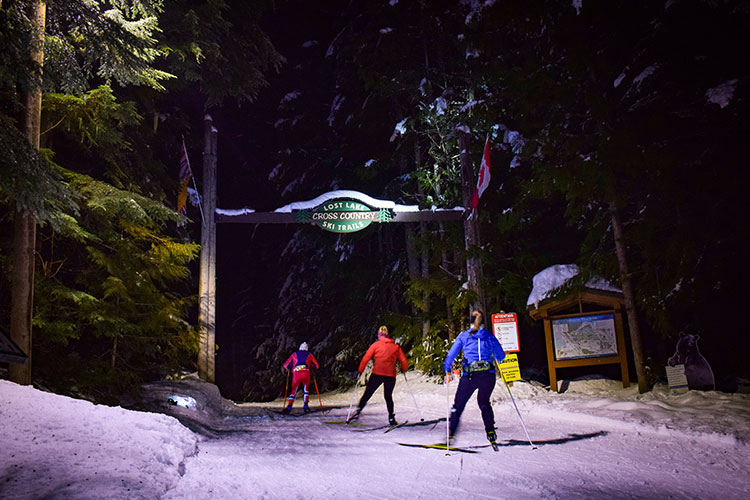 Three cross-country skiers head off on the Lost Lake trails at night in Whistler.