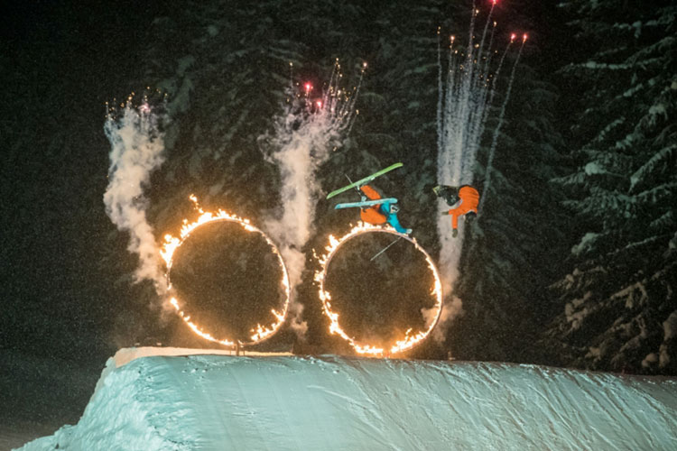 skiers and snowboarders jumping through flaming hoops