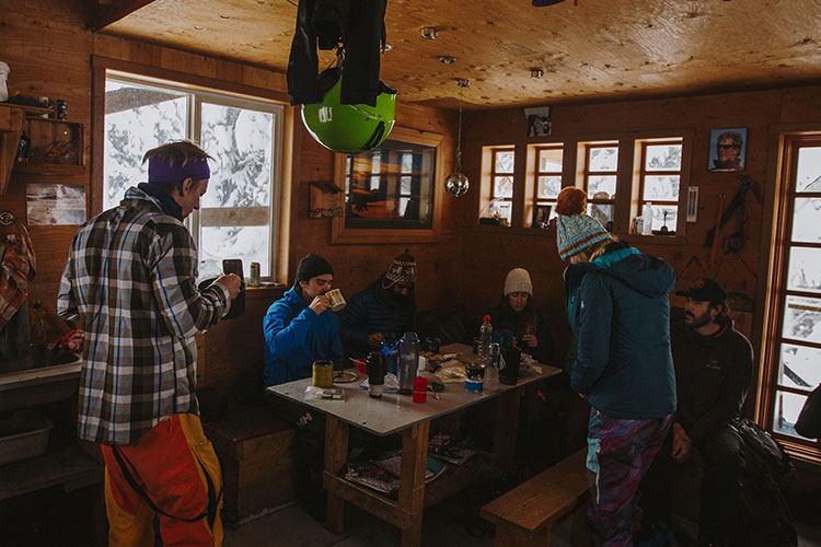 Friends inside a backcountry ski hut getting ready for the day ahead.