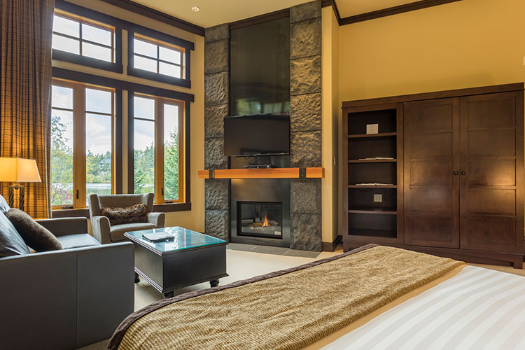 The inside of the Lakeview Studio Suite at Nita Lake Lodge has a fireplace, king bed, and comfy sofas.