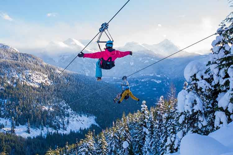 two people ziplining over snowy trees