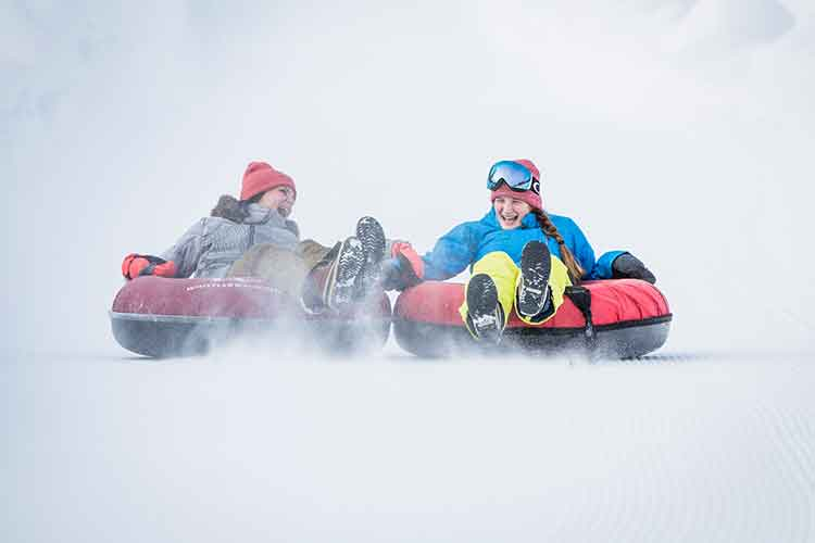 two people tubing on snow
