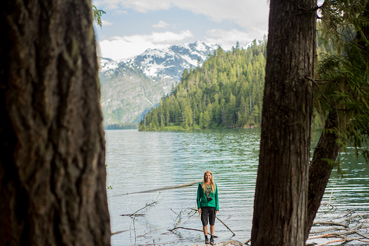 Hiker standing on log in Cheakamus Lake